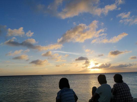 こちら、本島中部の北谷(ちゃたん)にあるサンセットビーチでス。 手前の3人はうちの嫁さんと娘2人。  「海に沈む夕日」を見たくて待ってたんですが、この後は水平線近くに雲があって、残念ながら沈む瞬間は見れませんでした。